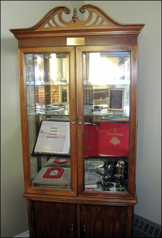 Items in the church display cabinet include Memorials in Remembrance of fellow parishioners, communion goblets, and United Church cake plates.