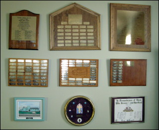 Plaques featuring those who have helped build the church through donations for pews and chairs, and lists of congregation members through the years.